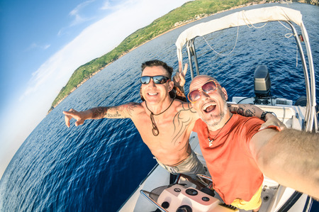 Adventurous best friends taking selfie at Giglio Island on luxury speedboat  Adventure travel lifestyle enjoying happy fun moment  Trip together around the world beauties  Fisheye lens distortion Archivio Fotografico