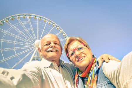 Gelukkig teruggetrokken senior paar nemen selfie op reis rond de wereld concept van actieve speelse ouderen met mobiele telefoon Oudere mensen plezier levensstijl in zonnige dag met sterk zonlicht kleurtonen Stockfoto