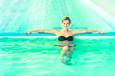 hydrotherapy: Beautiful woman in clear water looking at camera  Young girl swimming pool at exclusive resort  Medical concept of hydrotherapy spa treatment  Soft focus and natural light with bright vintage look