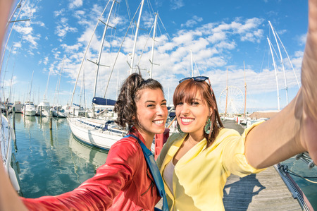 best friends: Young women girlfriends taking a selfie at harbour docks with sailboats