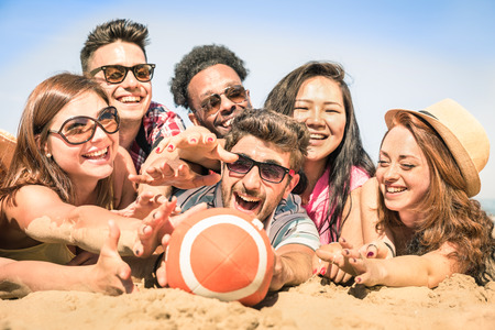 male friends: Group of multiracial happy friends having fun at beach games Stock Photo