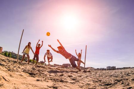 luz do sol: Amigos Multiracial jogando futebol na praia - Conceito de amizade de multi cultural se divertindo com jogos de verão - Backlight filtro marsala com auréola final da tarde sol e distorção da lente fisheye Imagens