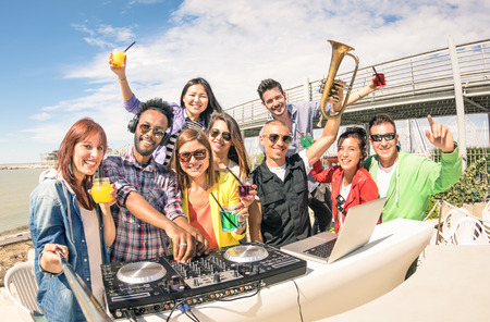 Funky hipster people taking selfie and having fun together at beach rave afterhour party - Summer festival moments with young disc jockey happy friends - Dj playing trendy sound at open air disco club Stock Photo