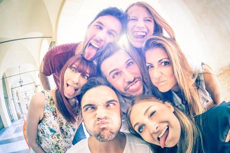 vysoká škola: Nejlepší přátelé, kteří se selfie venku se zadním osvětlením - Šťastný přátelství koncepce s mladí lidé spolu bavit - Cold vinobraní s filtrem vzhled s měkkým zaměřením na tvářích účinkem slunečního záření halo světlice Reklamní fotografie