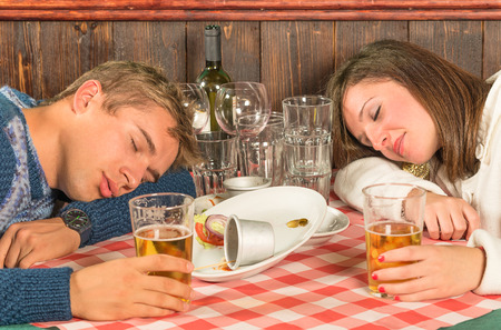 exceeding: Couple sleeping after a huge alcoholic Dinner Stock Photo