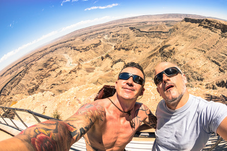 beauties: Adventurous best friends taking selfie at Fish River Canyon in Namibia - Adventure travel lifestyle enjoying happy fun moment - Trip together around the world beauties - Fisheye horizon distortion