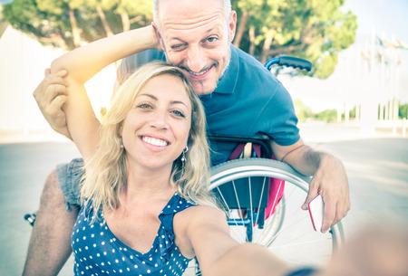 discapacidad: Pareja feliz en el amor tomar selfie de fondo urbano de la ciudad - concepto positivo de Discapacidad con el hombre en silla de ruedas - aspecto retro vintage filtrada con enfoque suave en mujer sonriente debido a la flama del sol de halo Foto de archivo