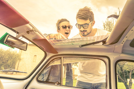 lost love: Couple of lovers looking at a map during honeymoon trip vacation - Vintage lifestyle traveling around the world with old retro classic car - Young people enjoying together happy moments of life