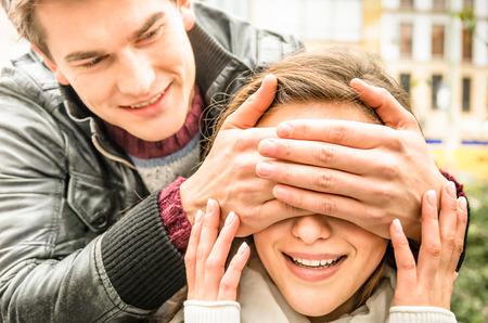 幸せな驚きガール フレンドの目を覆っている若い男 写真素材