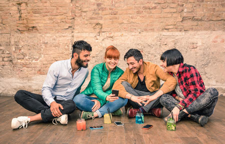 Group of hipster best friends with smartphones in grungy alternative location - Young entrepreneurs people resting at cocktail bar renovation - Friendship fun concept with trend technology interaction Archivio Fotografico