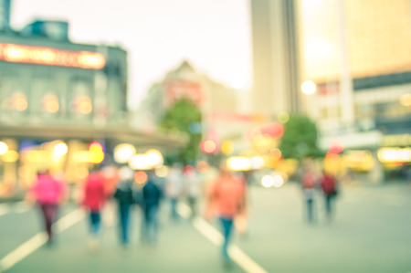 motion: Blurred defocused background of people walking on the road with vintage multicolored filter - Abstract bokeh of crowded Queen Street in Auckland city center during rush hour in urban business area Stock Photo