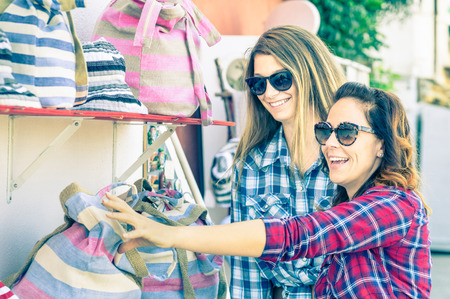 Young beautiful women girlfriends at flea market looking for bags - Best friends sharing free time having fun and shopping during travel - Soft vintage marsala filtered look - Focus on smallest girl Banque d'images