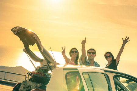 amistad: Mejores amigos animando en coche viaje por carretera al atardecer - Grupo de gente feliz al aire libre en viaje de vacaciones - Concepto de la amistad en los viajes con las emociones nostálgicas positivos - Foco suave debido al contraste de luz de fondo