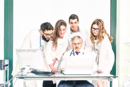 Groep jonge geneeskunde studenten met senior arts in de gezondheidszorg kliniek - Hogeschool medische leerlingen leren samen met de leerkracht op de computer - Ziekenhuis studio en de gezondheidszorg mensen