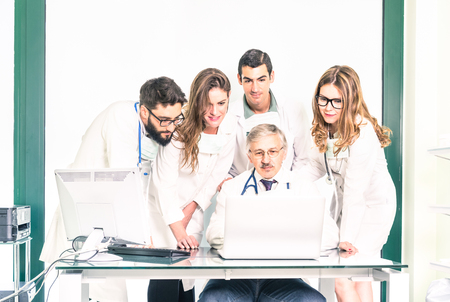 Group of young medicine students with senior doctor at health care clinic - University college medical apprentices learning together with teacher at computer - Hospital studio and healthcare people Standard-Bild