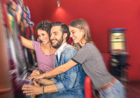 blurred people: Happy young friends having fun together with slot machine - Gambling concept with people playing at cash automatic devices in modern casino and resort - Blurred edges with soft radial zoom defocusing