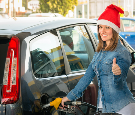 car gas: Young woman at gas station with Santa hat