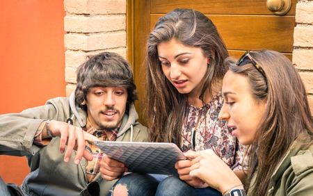 jovenes estudiantes: Amigos felices que se divierten con la tableta digital moderna - Estudiantes jóvenes que estudian junto al aire libre con el dispositivo electrónico - Universidad concepto de tiempo libre con la gente de la escuela secundaria - principales se centran en el hombre