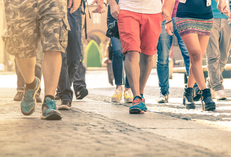 Crowd of people walking on the street - Detail of legs and shoes moving on sidewalk in city center - Travellers with multicolor clothes on vintage filter - Shallow depth of field with sunflare halo Stock Photo