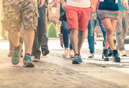 caminando: Multitud de personas caminando en la calle - Detalle de las piernas y los zapatos que se mueven en la acera en el centro de la ciudad - Viajeros con ropa multicolor en el filtro de la vendimia - poca profundidad de campo con halo sunflare