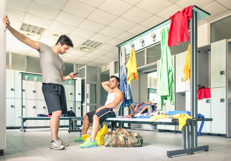 gym room: Young people at gym dressing room - Handsome guys at fitness studio doing their own staff before training - Social concept with lack of communication - Man looking at smartphone not talking to friend