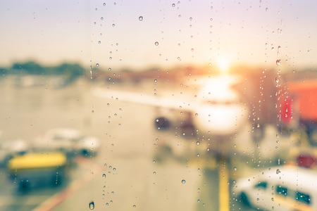 airport window: Abstract defocused bokeh of airplane at airport gate with sun coming out after the rain - Modern travel concept and wander lifestyle at sunset - Focus on raindrops with warm vintage filtered look Stock Photo