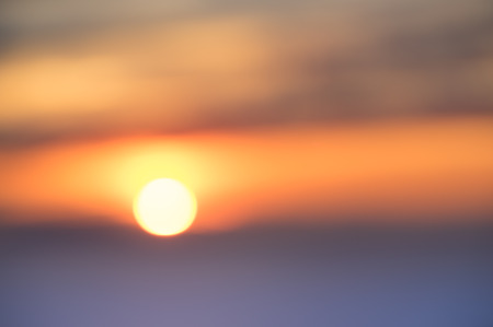 horizon over water: Blurred defocused background of sunset at the sea - Abstract bokeh of sun going down through the clouds over the horizon - Emotional concept of deep connection with nature wonders Stock Photo