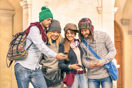 Gruppe von jungen Hipster Touristen Freunde mit dem Smartphone in der Altstadt, die Spaß - Reisen Lifestyle-Konzept mit glücklichen Menschen mit neuen Trendtechnologien verbunden - Warmer Herbst gefiltert Blick Standard-Bild - 46777716