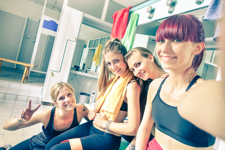 gym room: Happy girlfriends group taking selfie in gym dressing room - Sporty female friends ready for fitness time - Healthy lifestyle and sport concept in training center - Bright vintage desaturated filter