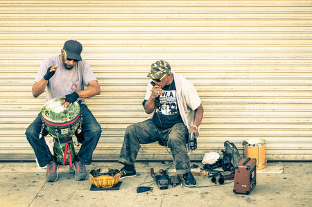 marginalization: VENICE BEACH - MARCH 20, 2015: musicians playing live on dirty sidewalk in Venice Beach Boardwalk. A lot of street artists are based performers at this place in the californian coast of Los Angeles