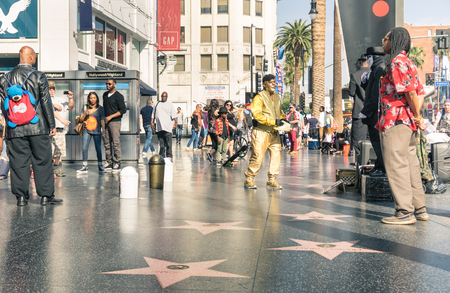 LOS ANGELES - MARCH 21, 2015: street artists and everyday multiracial people around the world famous Walk Of Fame in late afternoon on Hollywood Boulevard in LA California - United States of America