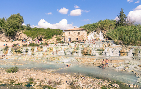 therapy geothermal: SATURNIA, ITALY - SEPTEMBER 24, 2015: international tourists swimming and relaxing in world famous hot springs in Saturnia at Mulino natural waterfalls by Manciano municipality in tuscan Maremma Editorial