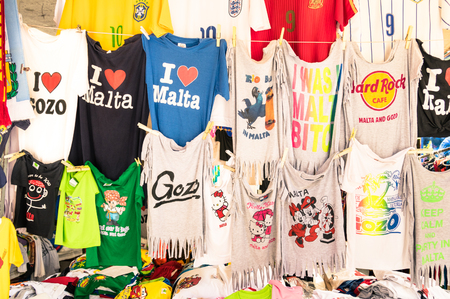 I T: LA VALLETTA, MALTA - OCTOBER 8, 2014: tshirts souvenir shop in the capital of world famous mediterranean island - T-shirts merchandising with common ads logos from worldwide companies and local places