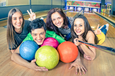 bowling alley: Best friends using selfie stick taking pic on bowling track - Friendship concept with young playful people having fun together - Soft focus on the guy with vintage filtered look and retro color tones Stock Photo
