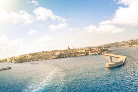 tilted view: Tilted horizon view of La Valletta before sunset from the sea - Travel and wanderlust concept with capital of world famous mediterranean island of Malta - Wide angle composition with cruise ship track Stock Photo
