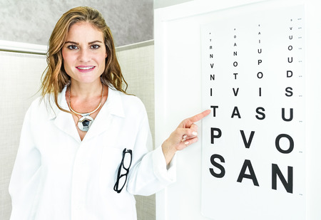 eyes: Female oculist doctor pointing at eye sight test chart and looking at camera - Optic medical concept in private clinic studio with young woman welcoming and cheering at patient