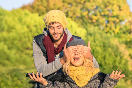 lovers park: Happy couple of lovers - Handsome man covering eyes to young surprised girlfriend - Love concept with hipster people wearing autumn fashion clothes outdoors - Late afternoon warm color tones