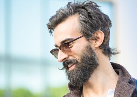estilo urbano: Retrato del individuo inconformista con confianza de cara expresi�n - modelo de moda masculina oto�o presenta al aire libre - hombre joven con barba y bigote alternativa - filtro retro suave y poca profundidad de campo Foto de archivo