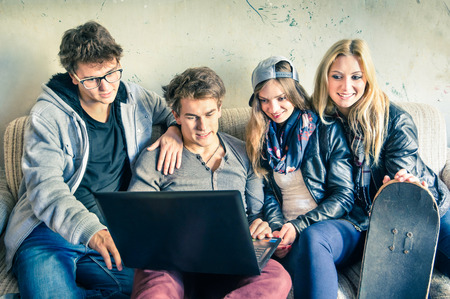Group of young hipster best friends with computer in urban alternative studio - Concept of friendship and fun with new trends and technology - Vintage filtered look with soft focus on guy with laptop