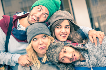 winter fashion: Group of best friends taking selfie outdoors with funny face expression and fashion clothes - Happy friendship concept with young hipster people having fun together - Vintage desaturated filtered look