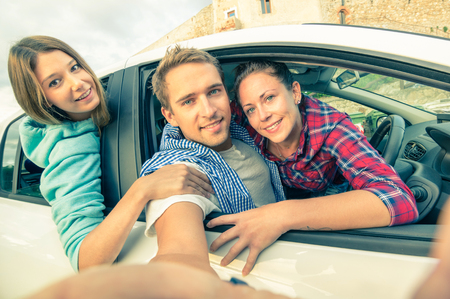 drive car: Handsome guy having fun with girlfriends - Best friends taking selfie at car trip on the road - Happy friendship and wanderlust concept with people traveling together - Soft vintage filtered look Stock Photo