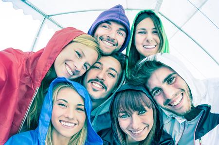 親友屋外パーカーを着て selfie を撮影 - カメラで一緒に楽しんで見て若い人たちと幸せな友情概念 - 冷たいシアン フィルター フレームの真ん中にフ 写真素材