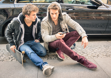 Young hipster fashion brothers having fun with smartphone - Best friends sharing free time with smart phone - Everyday life moments connected with modern devices - Soft focus on face of the guys