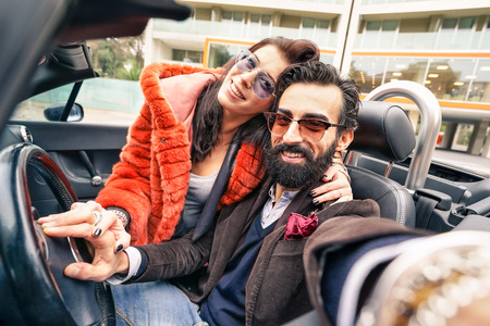 cabrio: Handsome hipster boyfriend having fun with girlfriend - Happy couple taking selfie at car trip - Modern love relationship concept with people traveling together - Main focus on face of the guy