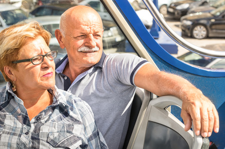 Happy senior couple in travel moment on sightseeing bus - Concept of active elderly during retirement - Wanderlust concept with mature people spending free time together - Sunny afternoon color tones