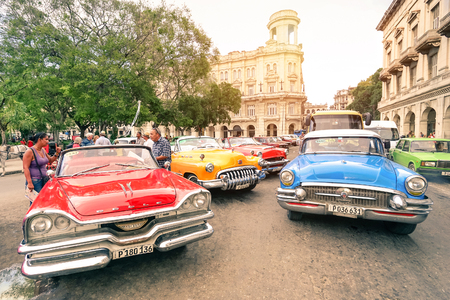 HAVANA, CUBA - NOVEMBER 17, 2015: multicolored vintage american cars in Havana City with National Museum of Fine Arts - Warm afternoon color tones with sunshine halo