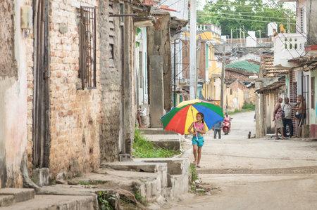 pobre: TRINIDAD, CUBA - 22 de noviembre, 2015: niño femenino paraguas multicolor recorre en la calle en la vieja banda de distrito. La ciudad es uno de los pueblos más antigua fundada por españoles - la Unesco Patrimonio de la Humanidad