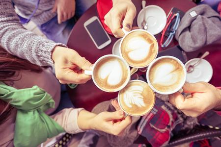 Groep vrienden drinken cappuccino bij coffee bar restaurant - Mensen handen juichen en roosteren met bovenste view point - Gezellig samenzijn concept met mannen en vrouwen - Vintage marsala gefilterde blik