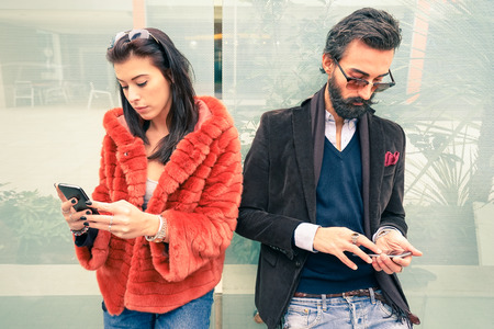 breakup: Hipster couple in sad moment ignoring each other using mobile phones - Concept of apathy sadness addicted to new technologies - Boyfriend and girlfriend break up with smartphones addiction