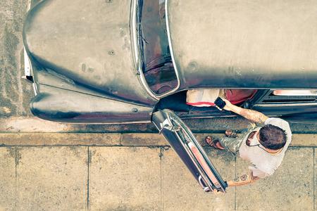 若い流行に敏感なファッションの男が次にスマート フォンを見て入れ墨をした彼のヴィンテージ車キューバ - 概念で道路の旅行中に新しいトレンドとレトロなライフ スタイルと混合技術のノスタルジックなフィルター外観 写真素材 - 50639747